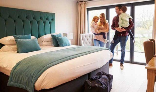 Famille devant un lit dans un hôtel